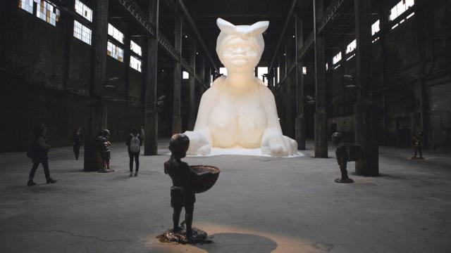 Kara Walker (2014) A Subtlety, or the Marvelous Sugar Baby an Homage to the unpaid and overworked Artisans who have refined our Sweet tastes from the cane fields to the Kitchens of the New World on the Occasion of the demolition of the Domino Sugar Refining Plant